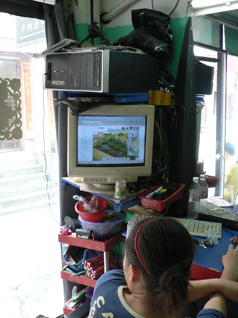 lady playing a game on a computer that is sitting on top of its monitor