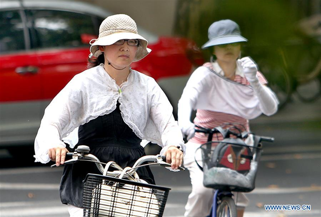 Two ladies riding with sun protective clothes in Hengshan Road, east China's Shanghai, 21 July 2017. The meteorological department of east China metropolis Shanghai recorded an air temperature of 40.9 degrees Celsius (105.6 degrees Fahrenheit) at around 2 p.m. Friday, the highest on record in the city in 145 years. Photo: Fan Jun / Xinhua
