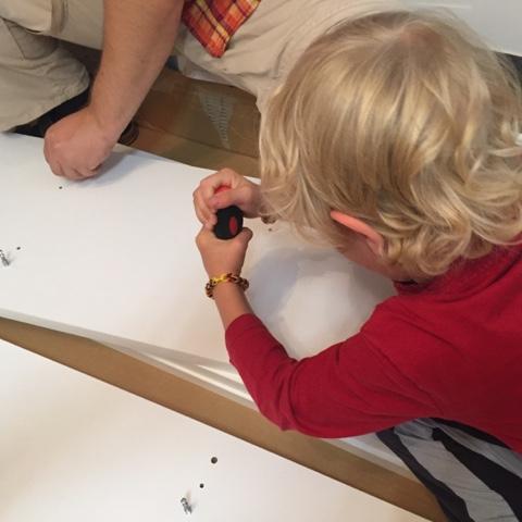 Kind hilft beim Möbelbau