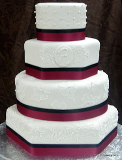 Four tier round and hexagon custom wedding cake with elegant brushed royal icing flowers, curlicues, monogram,edible pearls, garnet and black ribbons