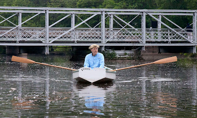 Andy Anderson in his replica rowing dingy  similar to boats that would have been used on the Hackensack many years ago in front of the 19th century swing bridge.