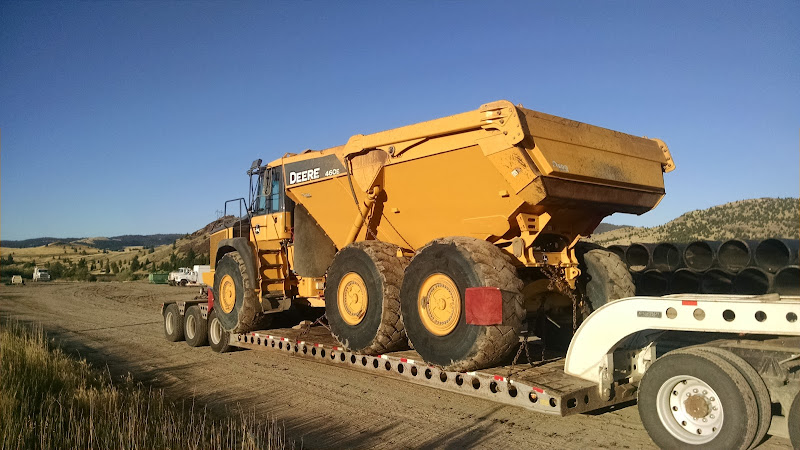 small articulating Deere dump truck loaded on flatbed trailer