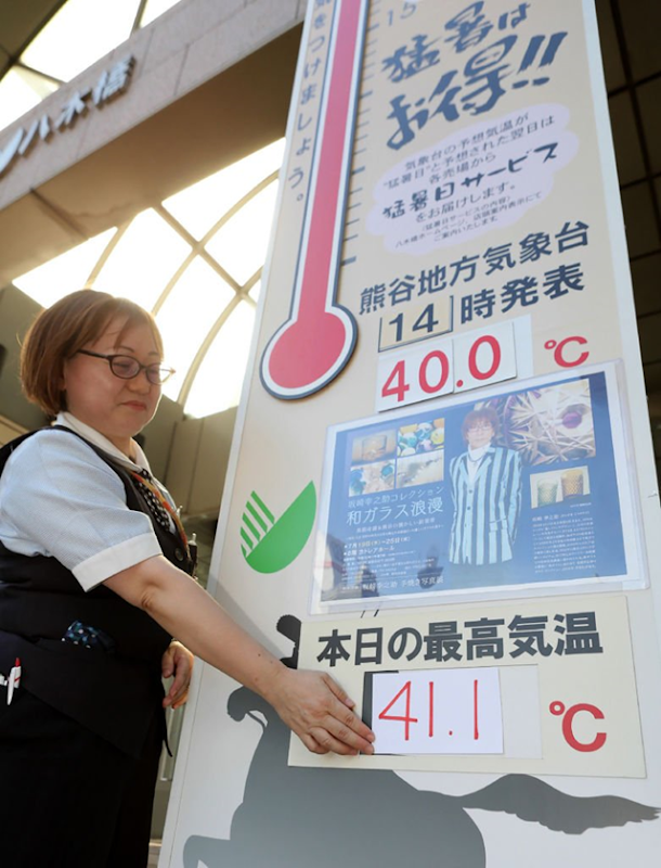 A department store employee places numbers showing a temperature of 41.1 degrees Celsius on a large thermometer board in Kumagaya, Saitama prefecture on 23 July 2018, which set a new all-time record for the hottest temperature ever measured in Japan. Photo: JIJI PRESS / AFP / Getty Images