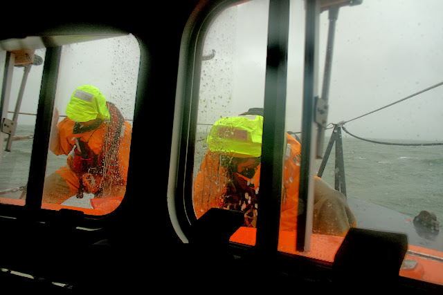 Poole crew members checking things on the foredeck during an exercise in rough weather - 26 January 2014 Photo: RNLI Poole/Rob Inett