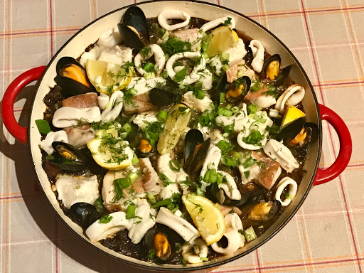 Spanish black paella with venere rice, mussels, squid and fish