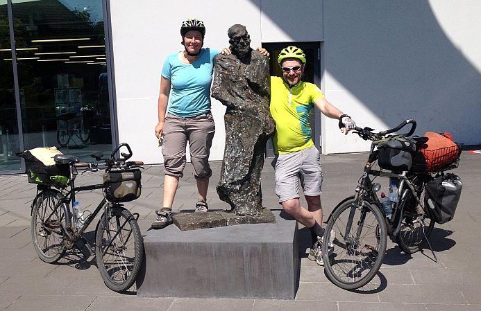 Miri und Chris mit dem Bronze-Denkmal vor dem Hanns-Dieter-Hüsch-Bildungszentrum in Moers