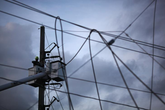 A worker of Puerto Rico's Electric Power Authority (PREPA) repairs part of the electrical grid after Hurricane Maria hit the area in September, in Manati, Puerto Rico, 30 October 2017. Photo: Alvin Baez / REUTERS