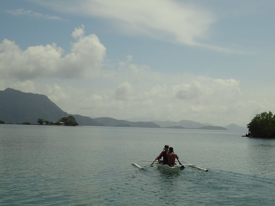 Nick and Tony paddling a banca boat out to the reef, Chindonan Island, Palawan, Philippines.