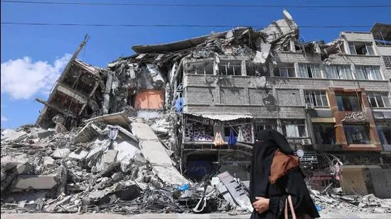 A Palestinian woman walks past a destroyed building in the Al-Rimal commercial district in the Gaza City on Saturday. (AFP)