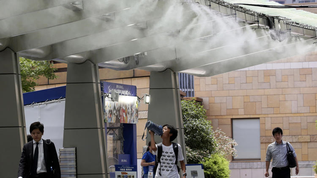 People cool down under the cooling mist spot in Tokyo, Monday, 13 July 2018. Searing hot temperatures are forecast for wide swaths of Japan and South Korea in a long-running heat wave. Photo: Koji Sasahara / AP