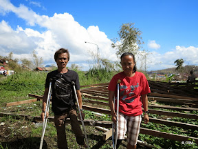 Two people standing next to collapsed building frame (they use crutches)