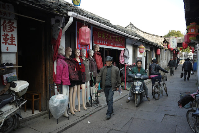man walking by mannequins at Xiaoshan Street in Shaoxing, China