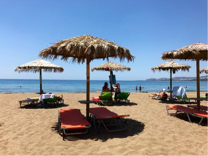 Strand med flere parasoller med tilhørende solsenger. Blått hav og blå himmel i bakgrunnen.