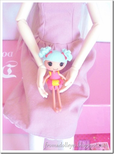 A Lalaloopsy blind bag doll being held by a msd sized ball jointed doll to compare the size.  The Lalaloopsy doll is dressed for the beach.