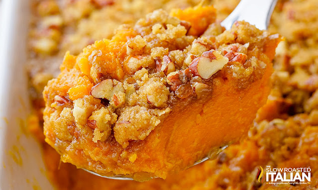 pecan sweet potato casserole being served out of casserole dish