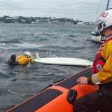 A Poole crew member inflates his lifejacket to support a windsurfer in the water - 28 September 2013. Photo credit: RNLI / Rob Inett