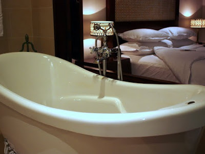 Bathtub and bed in a guest room at the Alila Sothea hotel in Siem Reap Cambodia