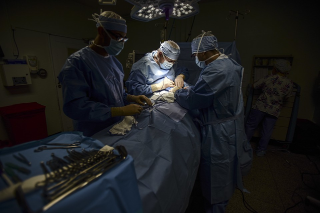 Surgeons work on a patient, in near-total darkness, at Dr. Isaac Gonzalez Martínez Oncological Hospital in San Juan, Puerto Rico. Photo: Carlos Giusti / AP