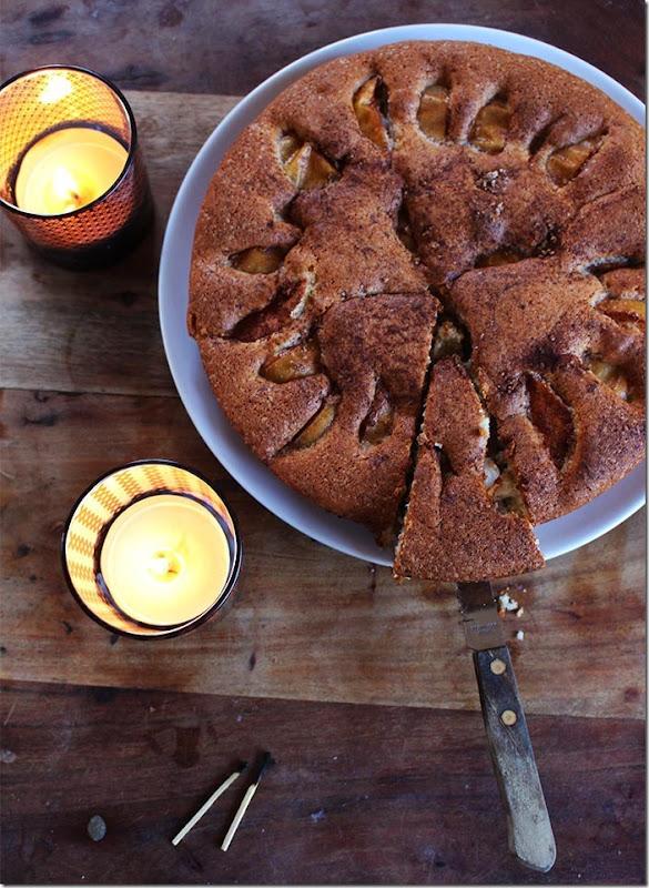 Bild från ovan på en uppskuren äppelkaka och tända ljus.