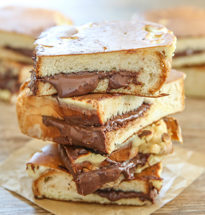 photo of a stack of Nutella Stuffed French Toast Pancakes with nutella oozing out