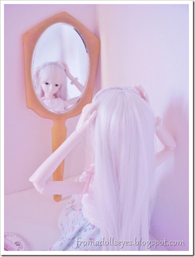 A ball jointed doll fixing her hair.