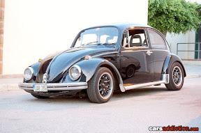 Black Volkswagen Beetle with black wheels