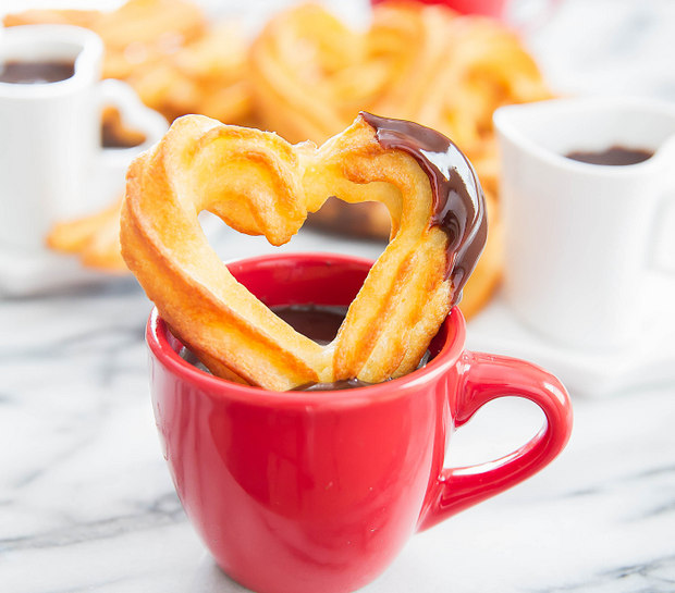 photo of heart-shaped baked churro on a mug of chocolate