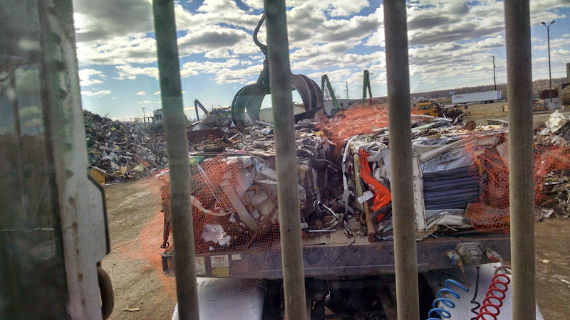 Truck driver's view of scrap metal being unloaded from a flatbed trailer through the rear cab window
