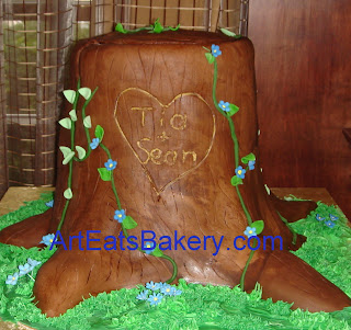 3D tree stump wedding cake with green vines and blue flowers