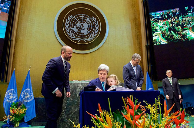 U.S. Secretary of State John Kerry signs the Paris Agreement at the UN in New York while holding granddaughter Dobbs Higginson on his lap. Scientists warn that the agreement is insufficient to prevent disastrous climate change. Photo: US Department of State