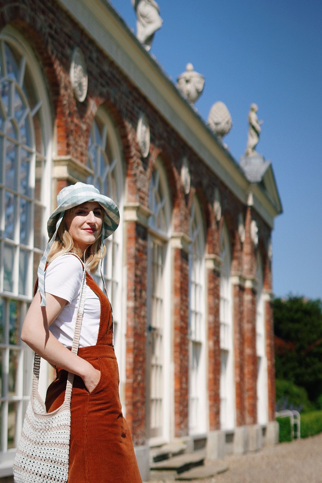 In the foreground, a girl turning to look at the camera, wearing a brown cord pinafore over a white t-shirt and a blue gingham bucket hat. In the background, a big brick greenhouse building with huge windows, filled with plants.