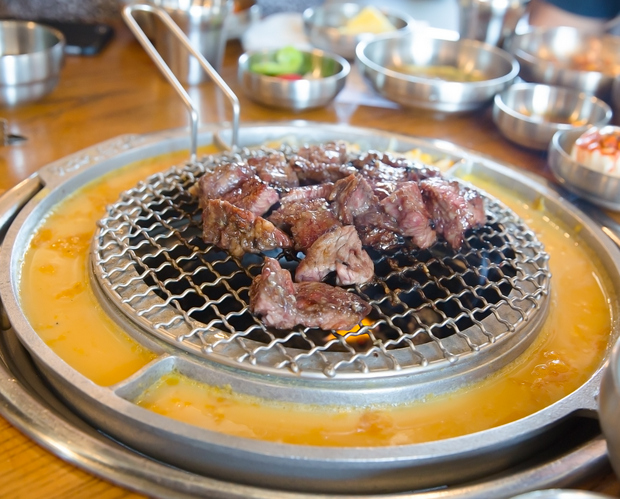 photo of the table grill with meat cooking on it