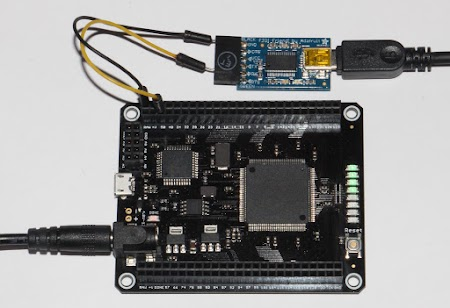 The Mojo FPGA board, connected to a serial-to-USB interface. The big chip on the Mojo is the Spartan 6 FPGA.