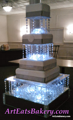 Four tier square modern wedding cake with silver gray ribbons, monogram and lighted crystal separators and stand