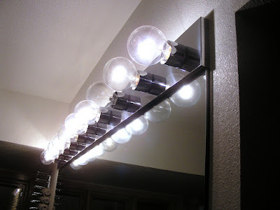One burned out bulb in a row of ten old-fashioned incandescent lightbulbs over bathroom vanity mirror