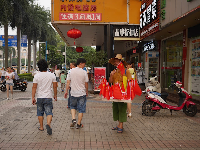 man selling PRC flags in Zhongshan, China