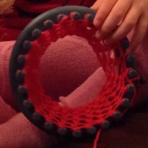 Kind strickt mit dem Strickring