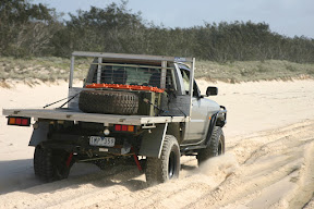 Ute driving through the sand on Fraser Island