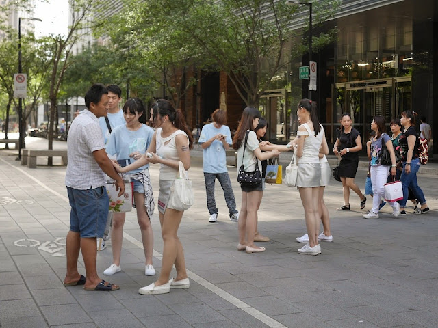 young women in silver skirts applying lotion to passers by in Taipei