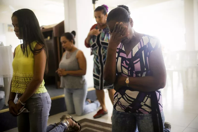 Women pray during Sunday mass in San Isidro, Puerto Rico, on 8 October 2017. Their neighborhood has been without grid electricity for more than two weeks. Photo: Mario Tama / Getty Images