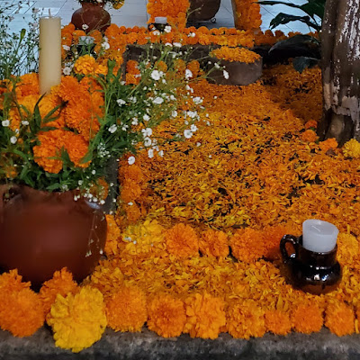 Marigolds. Lots of marigolds and their petals arranged and scattered around clay pots containing white candles and- even more marigolds.