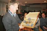 Henk ontvangt een klok met het logo van Pels en Pluim.