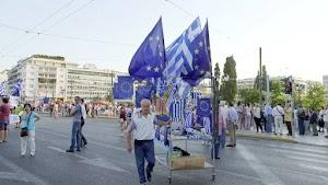 Demonstrant mit rollendem Bett und daran befestigten Griechenland- und Eurofahnen.