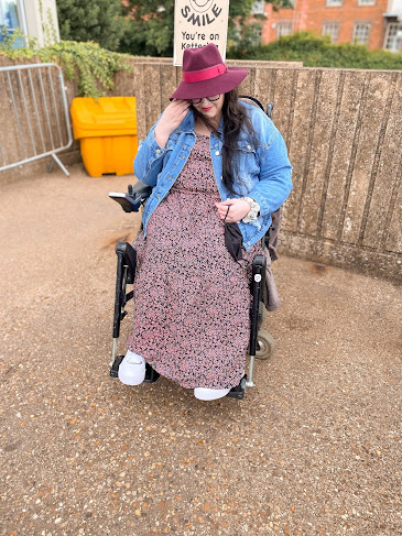 Plus size white woman sat in wheelchair wearing maxi floral dress, denim jacket, trainers and burgundy fedora hat