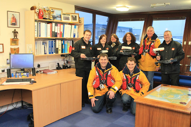 The B&Q 'just do it' team with Poole RNLI lifeboat crew L to R, Paul Taylor and Alex Evans, and Rod Brown, Lifeboat Operations Manager after they had 'made'over' the lifeboat station. 25 February 2013 Photo: RNLI/Claire-Marie Mason