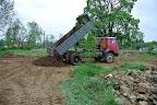 Ze zadní části pozemku jsme nechali dovézt lepší hlínu, aby se trávě a keříkům dařilo - v jílovité půdě plné kamenů by to neměly jednoduché...