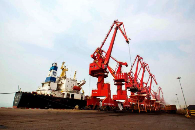 Imported coal being unloaded from a cargo ship at a port in Lianyungang, east China's Jiangsu province, on 29 March 2016. Photo: AFP