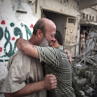 Palestinians hug each other after seeing their homes destroyed, during a 12-hour cease-fire in Gaza City's Shijaiyah neighborhood, Saturday, July 26, 2014. Gaza residents used a 12-hour humanitarian cease-fire on Saturday to stock up on supplies and survey the devastation from nearly three weeks of fighting, as they braced for a resumption of Israel's war on Hamas amid stalled efforts to secure a longer truce. (AP Photo/Khalil Hamra)