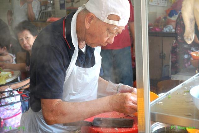 老翁用心的烹调鸡丝炒河粉