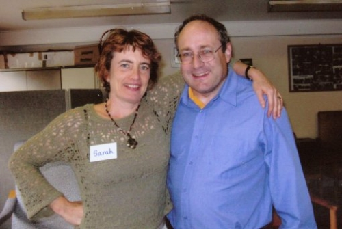 Woman with name tag 'Sarah', with arm around man in blue shirt and glasses